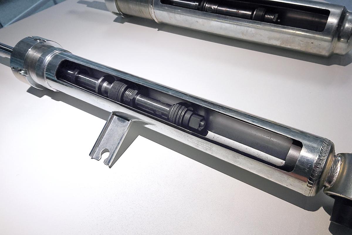 Новые амортизаторы в разрезе — передний (первый слайд), с дополнительным буфером на отбой, а задний (второй слайд), у него вспомогательный поршень работает при сжатие