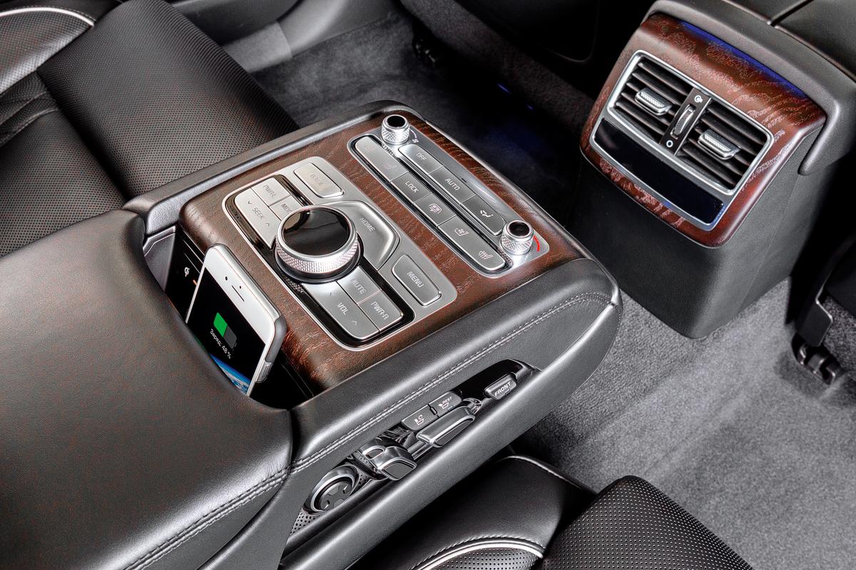 В откидном подлокотнике — россыпь приятных на ощупь металлизированных кнопок, качающийся контроллер управления мультимедиасистемой иудобный слот с беспроводной зарядкой длясмартфонов